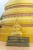Small golden statue of sitting Buddha. Small golden and beautifully detailed statue of sitting Buddha with a stupa in the background royalty free stock image