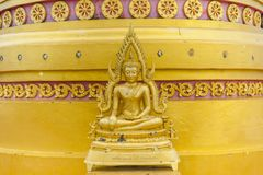 Small golden statue of sitting Buddha. Small golden and beautifully detailed statue of sitting Buddha with a stupa in the background royalty free stock photography