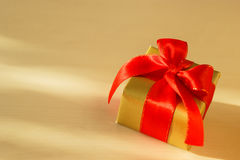 Small golden box with gift tied red bow. Holidays, present, christmas concept. Small golden box with gift tied decorative red bow Royalty Free Stock Photo