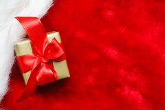 Small golden box with gift tied red bow. Holidays, present, christmas concept. Small golden box with gift tied decorative bow on red background Royalty Free Stock Photos