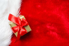 Small golden box with gift tied red bow. Holidays, present, christmas concept. Small golden box with gift tied decorative bow on red background Stock Image