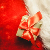 Small golden box with gift tied red bow. Holidays, present, christmas concept. Small golden box with gift tied decorative bow on red background Stock Photography