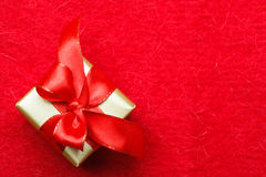 Small golden box with gift tied red bow. Holidays, present, christmas concept. Small golden box with gift tied decorative bow on red background with copy space Stock Photos