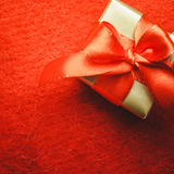 Small golden box with gift tied red bow. Holidays, present, christmas concept. Small golden box with gift tied decorative bow on red background with copy space Royalty Free Stock Images