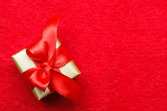 Small golden box with gift tied red bow. Holidays, present, christmas concept. Small golden box with gift tied decorative bow on red background with copy space Stock Photography