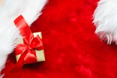 Small golden box with gift tied red bow. Holidays, present, christmas concept. Small golden box with gift tied decorative bow on red background Royalty Free Stock Image