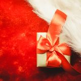 Small golden box with gift tied red bow. Holidays, present, christmas concept. Small golden box with gift tied decorative bow on red background Royalty Free Stock Images