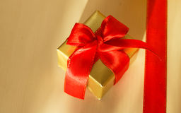 Small golden box with gift tied red bow. Holidays, present concept. Small golden box with gift tied decorative bow and red ribbon Royalty Free Stock Photos