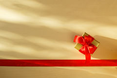 Small golden box with gift tied red bow. Holidays, present concept. Small golden box with gift tied decorative bow and red ribbon frame Royalty Free Stock Image