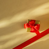 Small golden box with gift tied red bow. Holidays, present concept. Small golden box with gift tied decorative bow and red ribbon frame Stock Photography