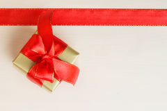 Small golden box with gift tied red bow. Holidays, present concept. Small golden box with gift tied decorative bow and red ribbon frame Royalty Free Stock Photography