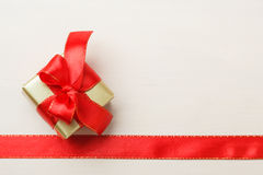 Small golden box with gift tied red bow. Holidays, present concept. Small golden box with gift tied decorative bow and red ribbon frame Stock Photo