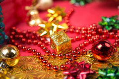 Small golden gift box near red bead and bow close-up Stock Photo