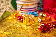 Small golden gift box near red bead and bow close-up Stock Photos