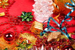 Small golden gift box near red bead and bow close-up Royalty Free Stock Image