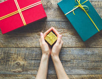 Small golden gift box on wooden background in hands. With ribbons and other box Royalty Free Stock Photo