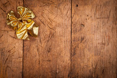 Small golden ribbon on wooden background. Small golden ribbon on rustic wooden background, Christmas concept Stock Photo