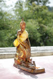 Small golden statue of a Buddha on the sanny day. In Thailand stock photos