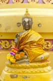 Small golden statue of sitting Buddha. Small golden and beautifully detailed statue of sitting Buddha with a stupa in the background royalty free stock photos
