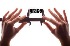 Small grace. Color horizontal shot of two hands holding a caliper and measuring the word grace Royalty Free Stock Photo