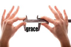 Small grace. Color horizontal shot of two hands holding a caliper and measuring the word grace Stock Photo