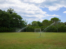Small grass soccer field irrigated by impact rotating sprinklers. Small grass soccer field irrigated with water sprays from impact rotating sprinklers. Trees and Royalty Free Stock Photos