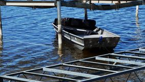 Small gray aluminum boat, used by dock installers to hold equipment, floats among lifts on a lake. Small gray aluminum boat, used by dock installers to hold stock video footage