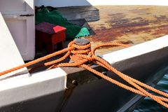 Small gray cleat with brown rope for boats Stock Photography