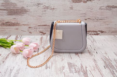 Small gray handbag with a price tag on a wooden background, pink tulips Royalty Free Stock Photo