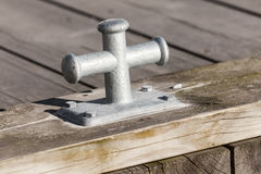Small gray mooring bollard on wooden pier Stock Photo