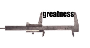 Small greatness. Color horizontal shot of a caliper, measuring the word greatness Stock Photography