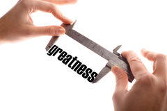 Small greatness. Color horizontal shot of two hands holding a caliper, measuring the word greatness Stock Images