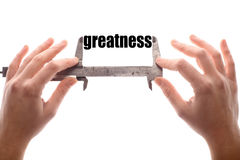 Small greatness. Color horizontal shot of two hands holding a caliper, measuring the word greatness Royalty Free Stock Images