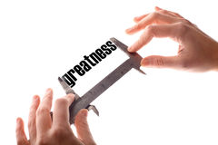 Small greatness. Color horizontal shot of two hands holding a caliper, measuring the word greatness Stock Image