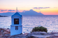 Small greek chapel and mount Athos at sunrise or sunset with sea panorama Royalty Free Stock Images