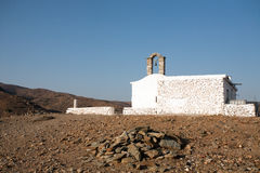 Small Greek church. From white stone on bright blue sky background Royalty Free Stock Photography
