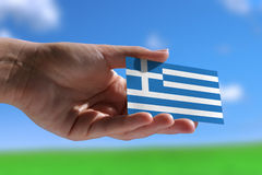Small Greek flag. Against sky with cumulus clouds Royalty Free Stock Photo
