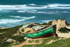 Small green boat. Green shipwrecked boat on coast Royalty Free Stock Image