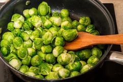 Small green cabbages of Brussels sprouts are stirred with a spatula in a frying pan. Kitchen top plate and stove on the stock photos