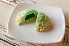 Small green cake with filling. Glazed dessert on white plate. Freshly cooked mint mousse cake. How about some sweets Royalty Free Stock Photography