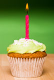 Small green cake with a single candle Stock Photo
