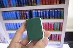 Small green cover book in finger with other books on shelf in b. Small  book in fingers with other books on shelf in background Stock Photos