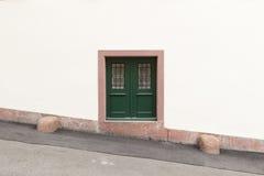 Small_green_door_white_wall-1 Στοκ εικόνα με δικαίωμα ελεύθερης χρήσης