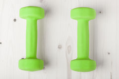 Small green dumbbells on wooden surface Stock Photography