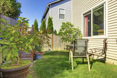 Small green fenced back yard with garden. Royalty Free Stock Images