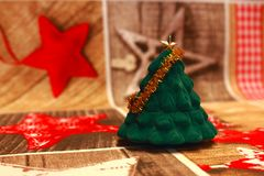 Small green fir herringbone with golden decoration on festive tablecloth s as New Year and Christmas decoration. Small green fir herringbone with golden Stock Photos
