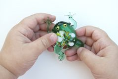 Small green frog made of glass in the hands of a child on a white background royalty free stock photo