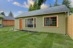 Small green guest house in the fenced backyard. Small guest house in the fenced backyard Royalty Free Stock Photo