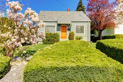 Small green house exterior with spring blooming trees. Stock Photo