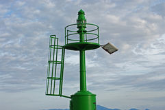 A small green lighthouse on the entrance of the harbor  of  Formia Italy. The lighthouse is fed by renewable energy Stock Photography